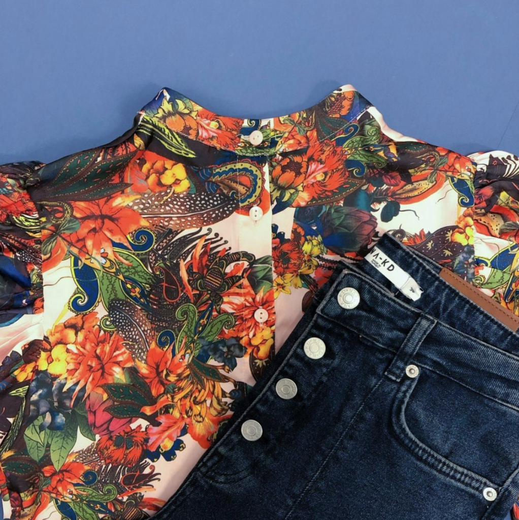Patterned top and blue jeans on blue background